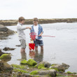 Two boys collecting shells on beach — Stock Photo #11881680
