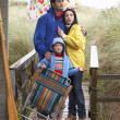Family on beach with umbrella - Photo