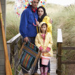 Family on beach with umbrella - Stockfoto