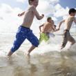 Teenagers playing on beach — Stock Photo