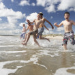 Foto Stock: Teenagers playing on beach