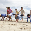 Teenagers playing on beach - Stock Photo
