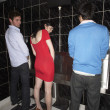 Woman and two men standing at mens urinal - Stock Photo