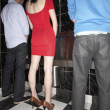 Woman and two men standing at mens urinal — Stockfoto