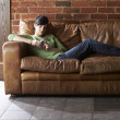 Stock Photo: Young woman with phone on sofa