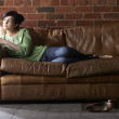 Young woman with phone on sofa — Stock Photo