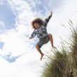 Boy jumping over dune — Stockfoto