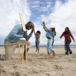 Family playing cricket on beach — Stock Photo