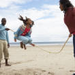 Family playing on beach — Stock Photo