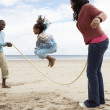 Family playing on beach - Foto Stock