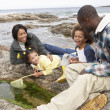 Royalty-Free Stock Photo: Young family with fishing net on rocks