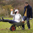 Young couple playing in wheelbarrow — Stock Photo