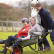 Stock Photo: Two young couples playing in wheelbarrow