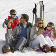 Young Family Sharing A Picnic On Ski Vacation - Stock Photo