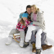 Young Family Sitting On A Sled In The Snow - Foto Stock