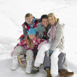 Stock Photo: Young Family Sitting On A Sled In The Snow