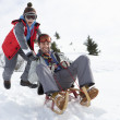 Stock Photo: Young Father And Son Sledding