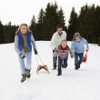 Young Family Running Through Snow With Sled — Stock Photo