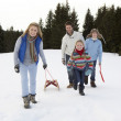 Stock Photo: Young Family Walking Through Snow With Sled