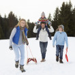 Young Family Walking Through Snow With Sled — Φωτογραφία Αρχείου