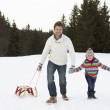 Young Father And Daughter Walking In Snow With Sleds — Stock Photo #11882783