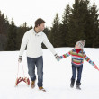 Young Father And Daughter Walking In Snow With Sleds - Stock Photo