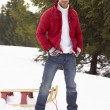 Young Man With Sled In Alpine Snow Scene — Stockfoto