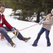 Young Girl Pulling Father Through Snow On Sled — Foto Stock