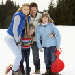 Young Family In Alpine Snow Scene With Sleds — Stock Photo
