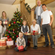 Family with gifts around the Christmas tree — Stock Photo