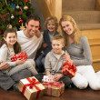 Family with gifts in front of Christmas tree — Stok fotoğraf
