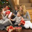 Family exchanging gifts in front of Christmas tree - Stockfoto