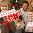 Family with gifts in front of Christmas tree - Stockfoto