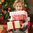 Young child holding gifts in front of Christmas tree — Stock Photo #11882819