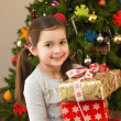 Young child holding gifts in front of Christmas tree - Stockfoto