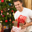 Young man holding gifts in front of Christmas tree — Stock Photo