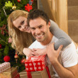 Young couple with gifts in front of Christmas tree — Stock Photo #11882826