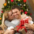 Young couple with gifts in front of Christmas tree — Stock Photo