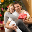 Young couple with gifts in front of Christmas tree — Stockfoto
