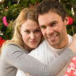 Young couple with gifts in front of Christmas tree — Stock Photo #11882829