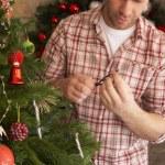 Young man fixing Christmas tree lights — Stock Photo