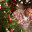 Stock Photo: Young mtrying to fix Christmas tree lights