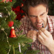 Young man trying to fix Christmas tree lights — Stock Photo