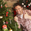 Young man fixing Christmas tree lights — Stock Photo