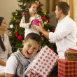 Hispanic family exchanging gifts at Christmas - Stock Photo