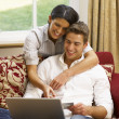 Young Hispanic couple shopping online - Stock Photo