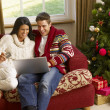 Young Hispanic couple Christmas shopping online — Stok fotoğraf
