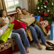 Hispanic mother and daughter resting after Christmas shopping — Stok fotoğraf
