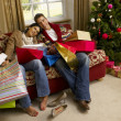 Young Hispanic couple resting after Christmas shopping — Stok fotoğraf