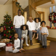 Mixed race family with Christmas tree and gifts — Stock Photo